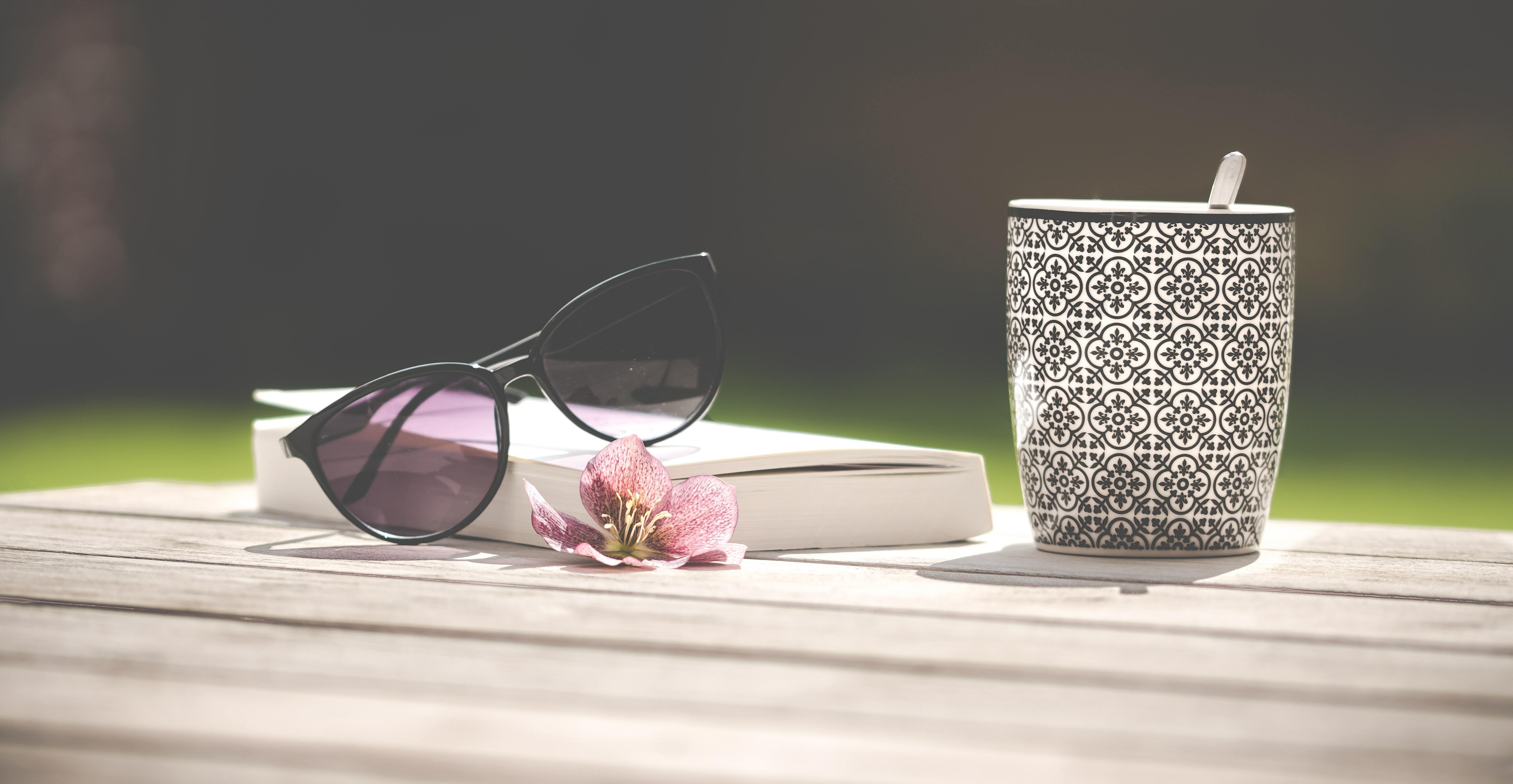 libro con gafas de sol y taza